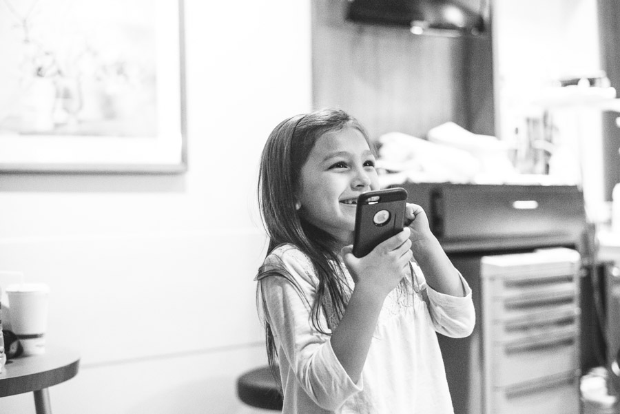 A young girl talking into a cell phone with a large smile on her face.