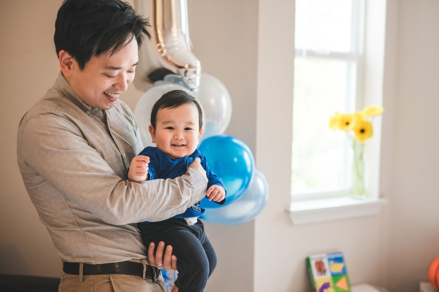 Smiling baby held by a man