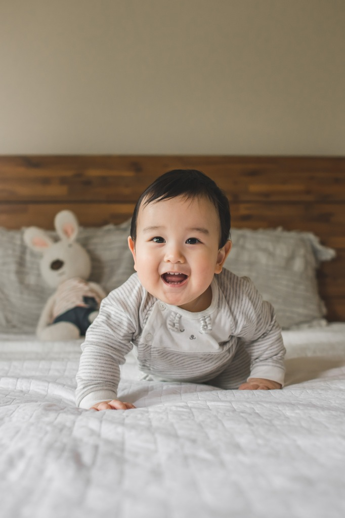 Baby crawling on a bed smiling in Issaquah