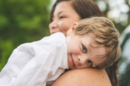 Young boy smiling on his mother's shoulder by a Seattle Family Photographer