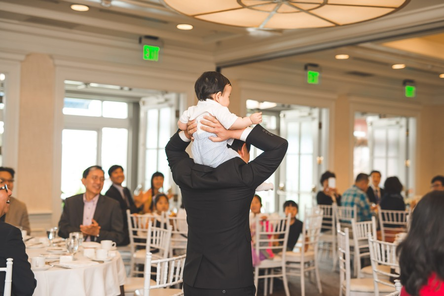 Father holding son on his shoulders in a party room