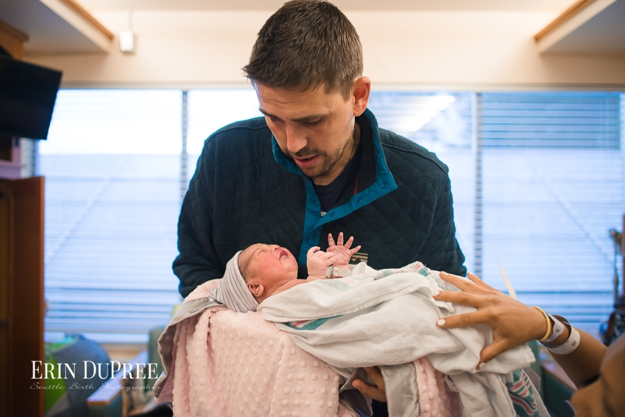 Father holding newborn baby by hospital bed by Seattle Birth Photographer