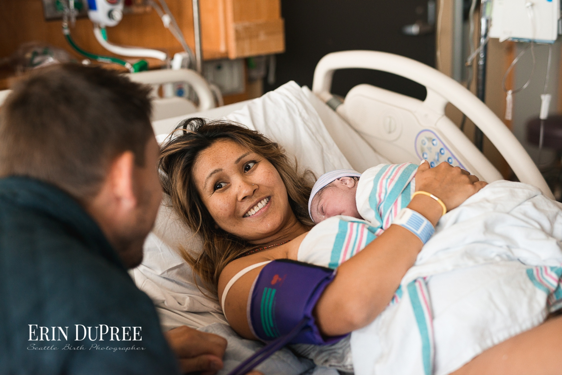 Mom smiling holding newborn baby in hospital by Seattle Birth Photographer
