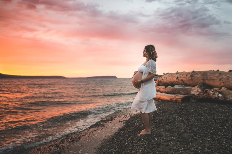 Pregnant woman on a beach at sunset with pink and orange sky by Seattle Maternity Photographer