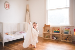 Toddler girl holding up a blanket