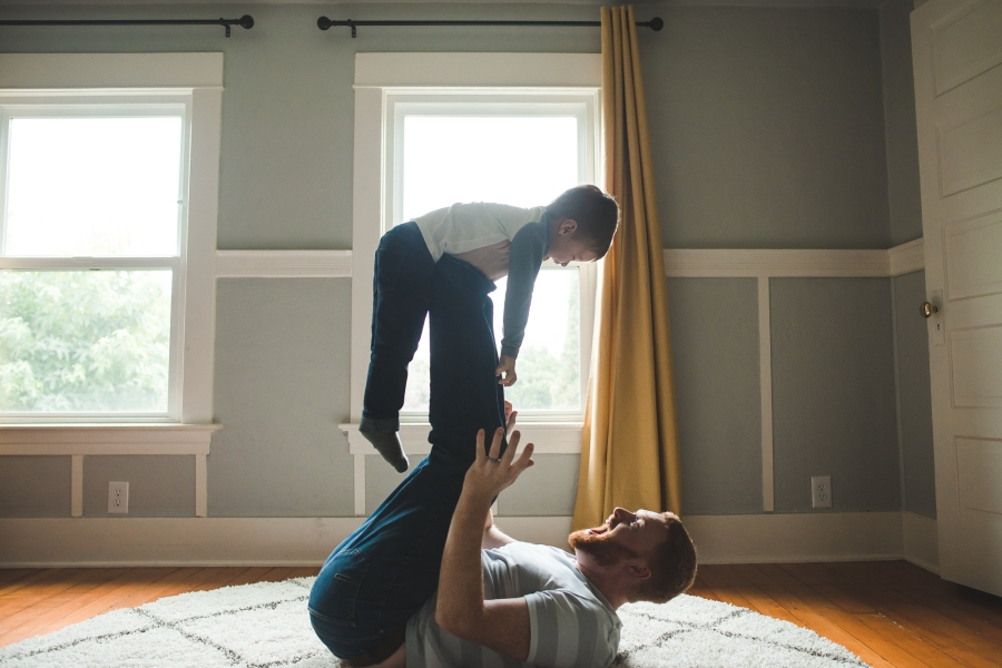 Father lifting toddler son in the air with his feet by Seattle Newborn Photographer