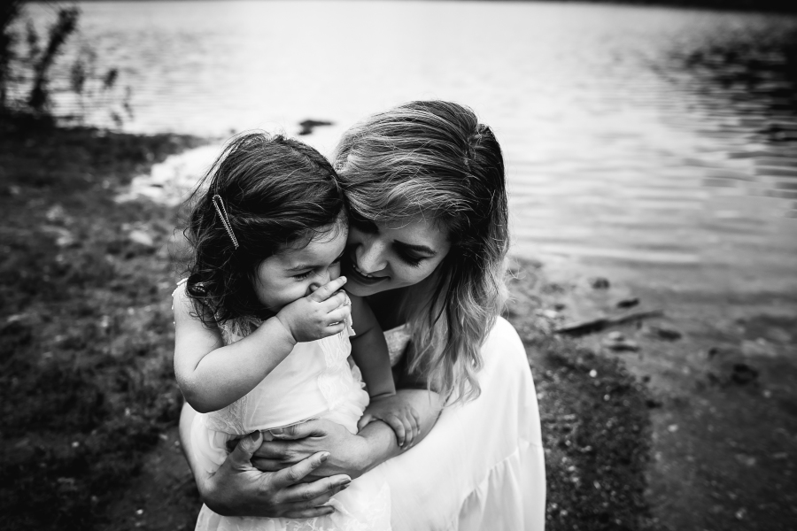 Black and white photo of a mother and child by a lake with Seattle family photographer